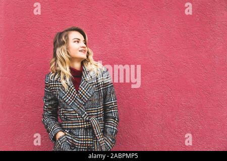A modern stylish Caucasian girl in a plaid coat against the background of a bright wall looks thoughtfully to the side. - Stock Photo