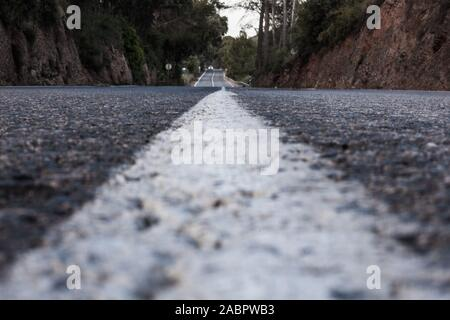 Road in low perspective from the asphalt with a car in the distance