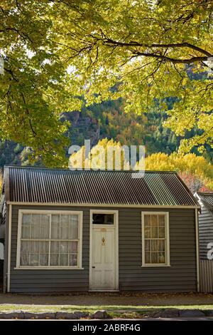 An Historical Cottage Against Golden Autumn Foliage In Arrowtown, New Zealand - Stock Photo
