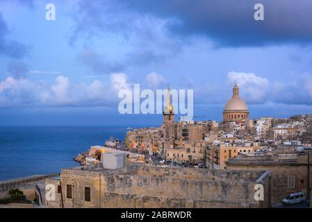 Skyline of Valletta at sunset with Basilica and St. Paul's Anglican Cathedral. Malta