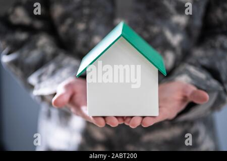 Mid Section Of Soldier Holding Model House In Hand - Stock Photo