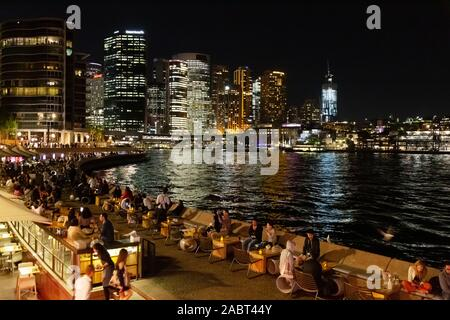 Sydney Night; Sydney Harbour and Circular Quay at night, with skyscrapers and people eating at the Opera Bar in spring; Sydney Australia