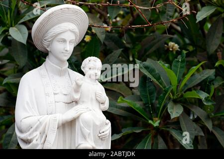 Statue of Our Lady of La Vang in Ao Dai dress.  Phu Cam Cathedral.  Hue.  Vietnam. - Stock Photo