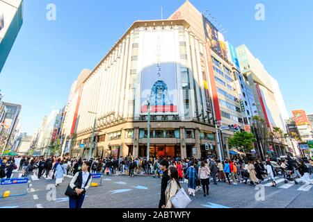 The Ginza 4 crossroads with the Mitsukoshi store. Busy with people crossing the street when part of Chou Dori is a pedestrian precinct at weekends. - Stock Photo