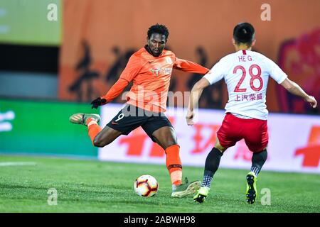 Senegalese football player Makhete Diop of Beijing Renhe F.C., left, keeps the ball during the 29th round match of Chinese Football Association Super League (CSL) against Shanghai SIPG in Beijing, China, 27 November 2019. Beijing Renhe tied the game with Shanghai SIPG with 3-3. - Stock Photo