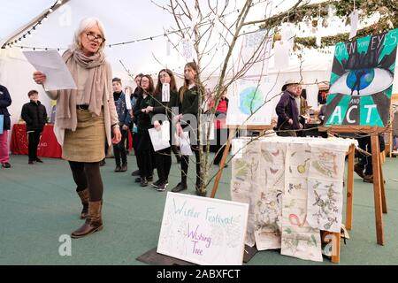 Hay Festival Winter Weekend, Hay on Wye, Powys, Wales, UK - Friday 29th November 2019 - Poet Nicola Davies reads beside a Wishing Tree with local school students as part of the local Youth Climate Strike - Credit: Steven May/Alamy Live News - Stock Photo