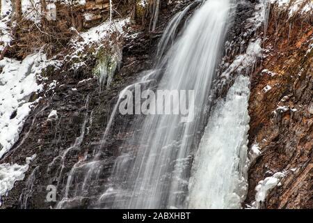 Stunning frozen waterfall on rocky mountain - Stock Photo