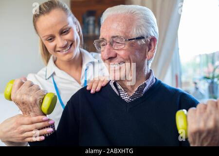 Female Physiotherapist Helping Senior Man To Lift Hand Weights At Home - Stock Photo