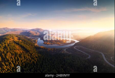 Aerial drone view over the autumn mountains with mountain road serpentine, river and forest. Landscape photography