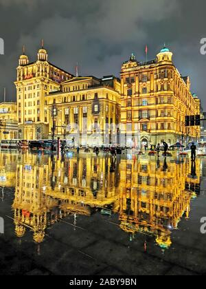 Night view of a reflection of the illuminated century-old western-style buildings on the wet ground in the rain at the promenade along the Bund in Sha - Stock Photo