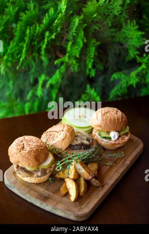 three mini burgers served with fries on wood serving board - Stock Photo