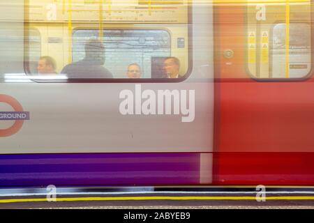 Moving London Underground tube train with people on - Stock Photo