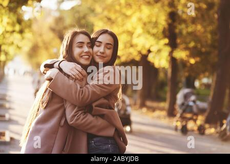 Side profile of young smiling brunette twin girls hugging and having fun in casual coat standing close to each other at autumn sunny park alley on - Stock Photo