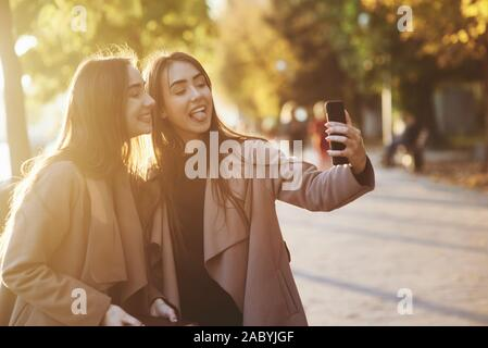 Side view of young, pretty, brunette twin girls making funny faces while taking a selfie with black phone, wearing casual coat and standing at autumn
