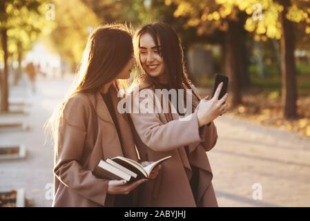 Young smiling brunette twin girls looking at each other and taking selfie with black phone, while one of them is holding books, wearing coat, standing
