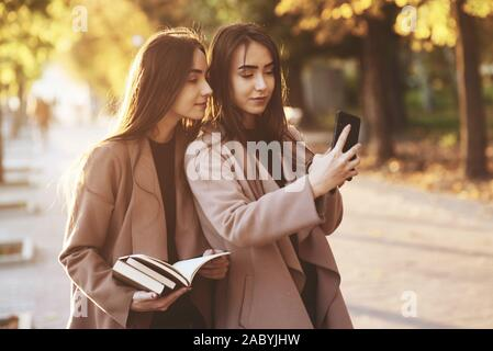 Young pretty brunette twin girls looking at each other and taking selfie with black phone, while one of them is holding books, wearing coat, standing