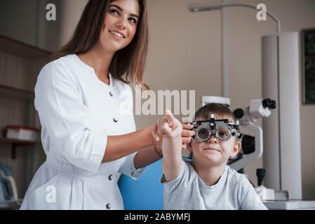 Kid showing something with his forefinger. Child sitting in the doctor's cabinet and have tested his visual acuity - Stock Photo
