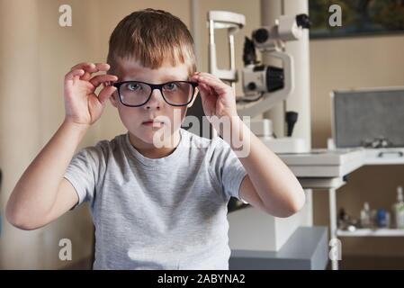 Touching new device. Portrait of kid sitting with glasses in doctor clinic with ophthalmic equipment at background - Stock Photo