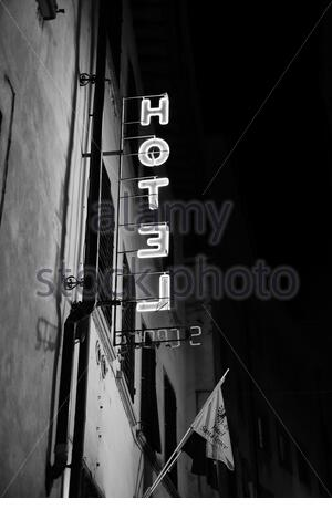 Hotel brightly illuminated neon sign at night - Stock Photo