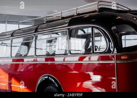 Vintage red bus parked indoor. White room with windows. Car show - Stock Photo