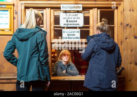 Two female mountain hikers talking to a woman at the reception desk of the Berliner Hütte, Zillertal, Tyrol, Austria - Stock Photo