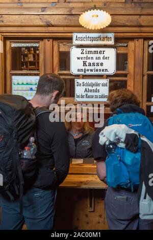 Mountain hikers talking to a woman at the reception desk of the Berliner Hütte, Zillertal, Tyrol, Austria - Stock Photo