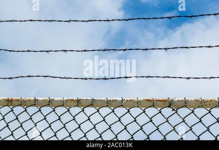 three rows of barbed wire above a chain link fence at a prison under blue skies on a sunny day - Stock Photo