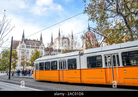 Budapest, Hungary - Nov 6, 2019: Public yellow tram riding in front of the Hungarian Parliament building. Hungarian capital city public transport. City transportation. Tourist attraction. - Stock Photo
