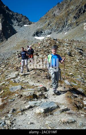 Four male hikers descending through steep terrain from the Mörchenscharte into the Floitengrund on the Berliner Höhenweg, Zillertal, Tyrol, Austria - Stock Photo