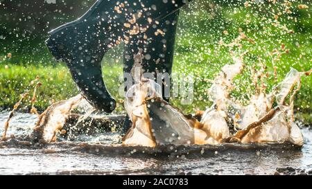 green wellington  boots splashing in wet muddy puddles in the early morning light  copy space to side of image - Stock Photo