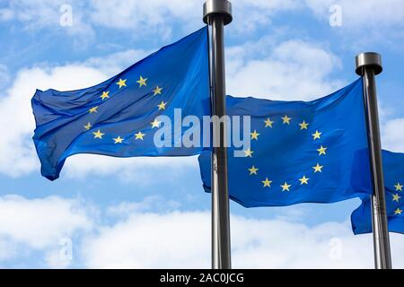 Close up of two European Union Flags flying outside the Berlaymont Building in Brussels, Belgium. - Stock Photo