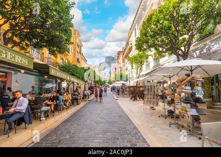 Tourists and local Monegasque enjoy a sunny summer day shopping and dining in Monte Carlo, Monaco, with the steep mountains in the distance. - Stock Photo