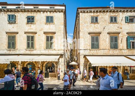 Tourists walk the main street or Stradun as they pass a narrow staircase up to the wall in the walled city of Dubrovnik Croatia. - Stock Photo