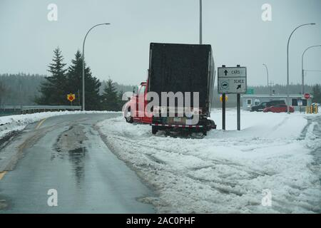 Semi truck off the road at check station during bad road conditions and accidents in first winter storm of the season - Stock Photo
