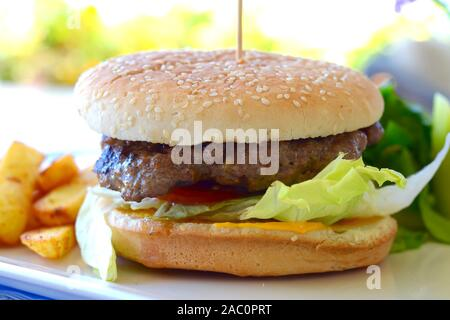 HOME MADE BEEF BURGER in a white seeded bun and salad garnish - Stock Photo