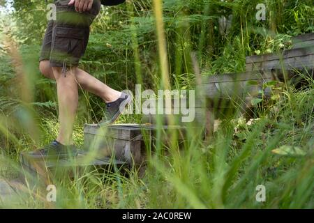 Woman in shorts and sneakers, with a city backpack, descends down the wooden steps, among the tall, green grass. Active lifestyle concept. - Stock Photo