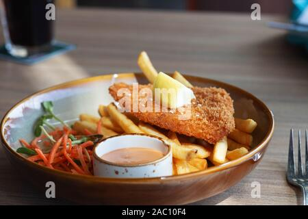 fried fish filet with french fries and veggies on plate in restaurant