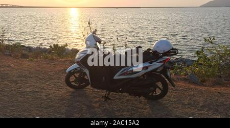 Langkawi, Malaysia - Mar 29, 2019. A scooter parking near the sea in sunset. Langkawi is an archipelago of 99 islands in the Andaman Sea. - Stock Photo