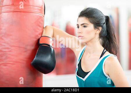 Female boxer leaning on a boxing bag, looking confidently in front of her - Stock Photo