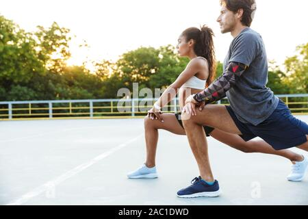 Image of an amazing young strong sports couple man and woman make stretching exercises outdoors.