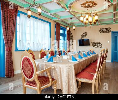restaurant room with classic golden chairs with red fabrics, turquoise doors and windows