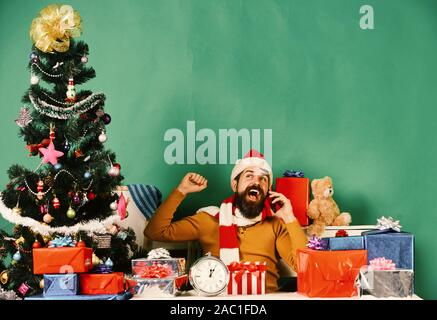 Man with beard and excited face sends greetings on New Year. Christmas eve and congratulations concept. Santa holds cellphone. Santa Claus talks on mobile phone near fir tree on green background - Stock Photo