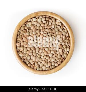 Uncooked lentils in wooden bowl isolated on white background with clipping path - Stock Photo