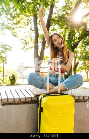 Photo of teenage tourist girl laughing while sitting with luggage on bench in green park - Stock Photo