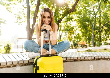 Photo of beautiful tourist girl smiling while sitting with luggage on bench in green park - Stock Photo