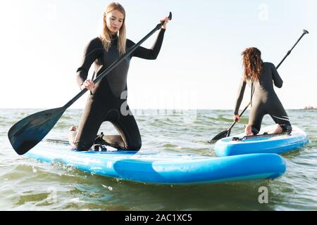 Image of a young beautiful two women on a kayaks outdoors at the beach. - Stock Photo