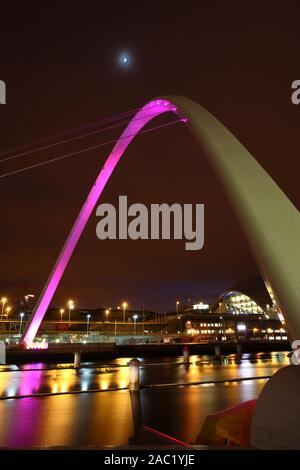 Night Time view of the Millenium Bridge looking towards Gateshead, Tyne and Wear with the Moon in the Sky. - Stock Photo
