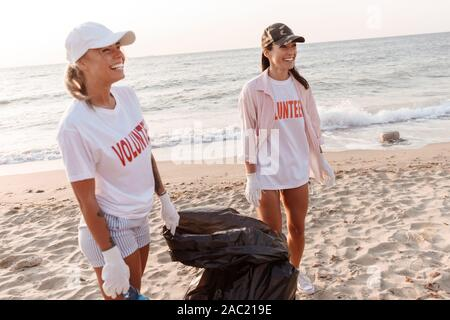 Group of young people volunteers cleaning beach from rubbish - Stock Photo