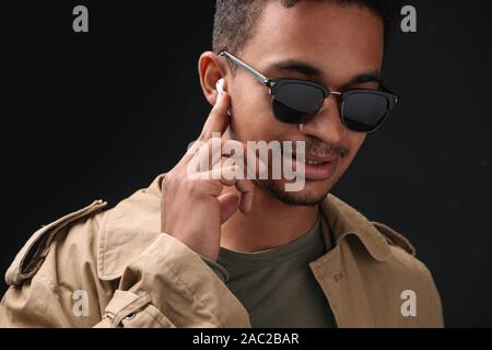 Image of serious african american guy in sunglasses using earbuds isolated over black background - Stock Photo