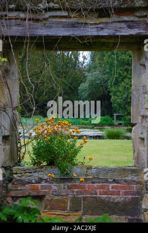 Garden ornaments. Window with flower in an English garden.